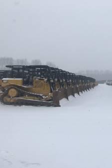 Sneeuwschuivers keurig op een rij, werkloos in de sneeuw