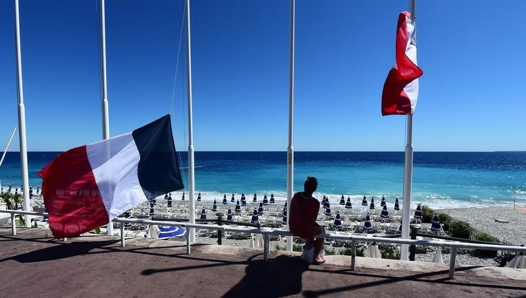 Een vrouw zit bij het strand van Nice naast een Franse vlag die halfstok hangt. Beeld afp