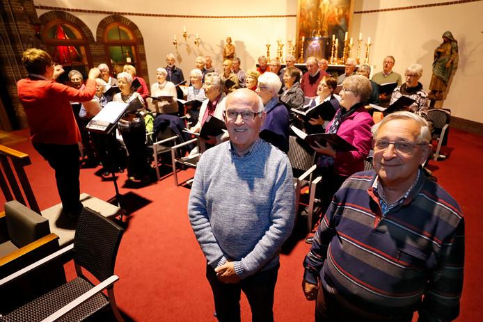 Penningmeester Theo Wouters en voorzitter Jo van den Biggelaar met op de achtergrond het jubilerende Willibrorduskoor uit Waalre.