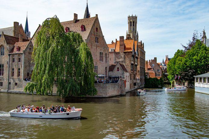 Een toeristenbootje vaart voorbij de Rozenhoedkaai, een hotspot van Brugge.