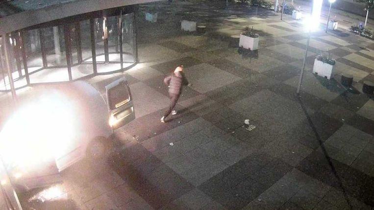 De verdachte loopt weg nadat hij de auto in brand heeft gezet.