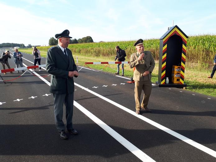Een Nederlandse en Belgische douanier verzorgen op ludieke wijze de opening van de randweg rond Baarle-Nassau.