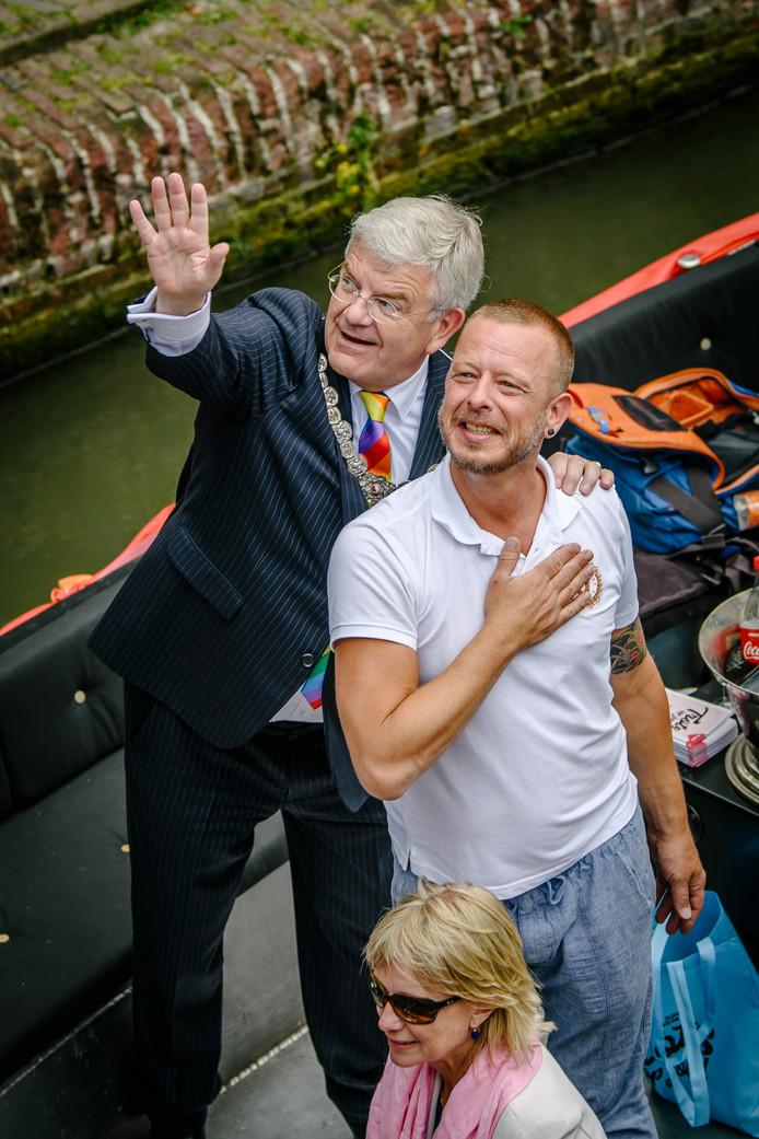 Burgemeester Van Zanen zwaait samen met organisator Robbert Kalff naar mensen op de kade.