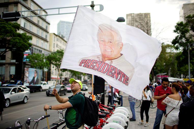 Een aanhanger van presidentskandidaat Andres Manuel Lopez Obrador zwaait met een vlag met diens beeltenis en daaronder de benaming 'president'.