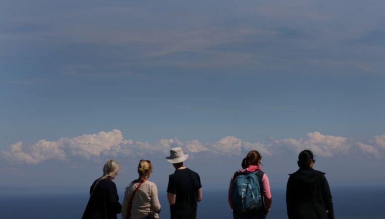 Leden van de Britse Cloud Appreciation Society turen naar de lucht op het Britse eiland Lundy. De organisatie met duizenden leden bewondert wolken. Het is pure kunst, het is nooit hetzelfde en iedereen kan er altijd van genieten, staat in haar manifest. Het beschouwen van de wolken versterkt de ziel. Beeld REUTERS