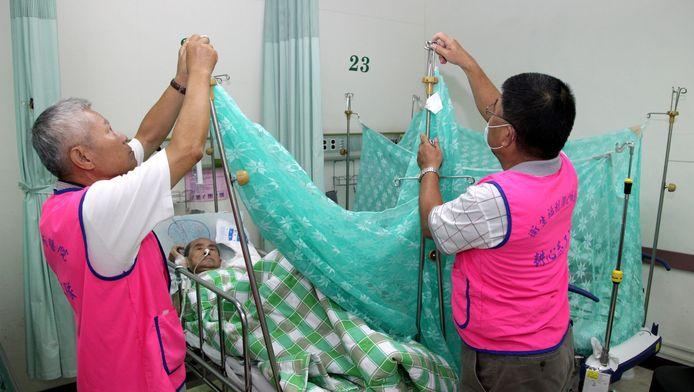Ziekenhuismedewerkers behandelen een patiënt met knokkelkoorts