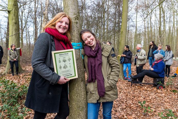 Sterre Westenbrink (links) en Saré Geurts van studievereniging STORM bij hun geadopteerde boom.