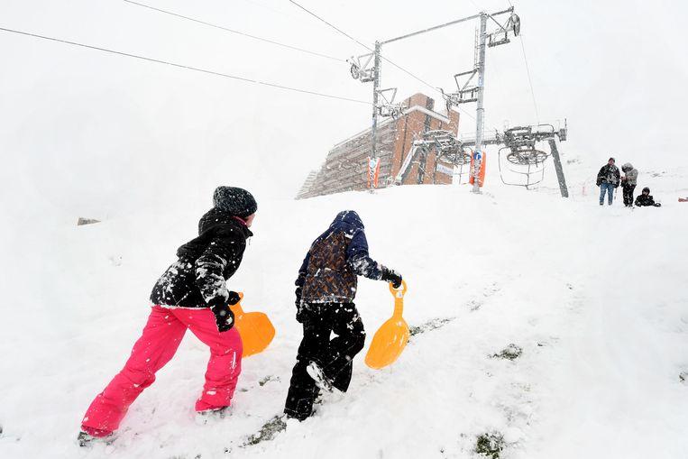 Kinderen lopen met scheppen in de sneeuw.