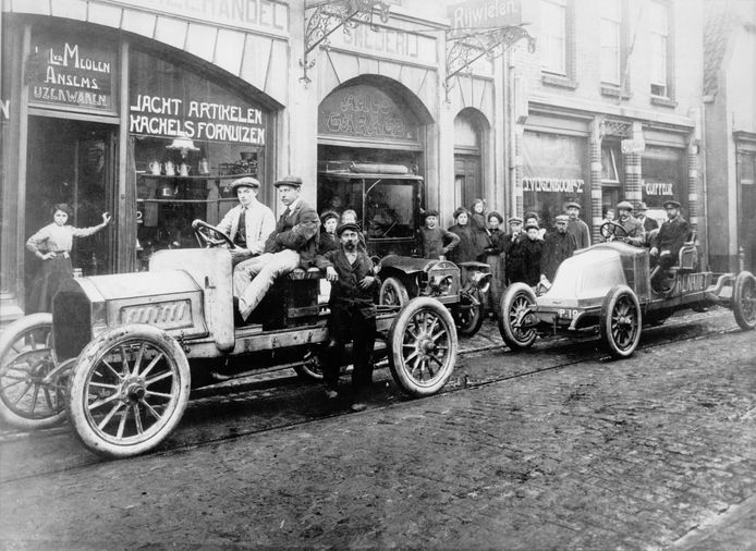 Garagehouder Jos van der Meulen voor de linkse auto in de Helmondse Kerkstraat (nu Kerkstraat Zuid), op een foto uit begin twintigste eeuw.