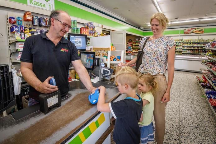 Buurtsuper Attent Hof bestaat 25 jaar. Mede-eigenaar Marc Hof (links) bezorgt de boodschappen aan huis. En kinderen, zoals die van Karin Mulder, krijgen nog altijd een snoepje aan de kassa.