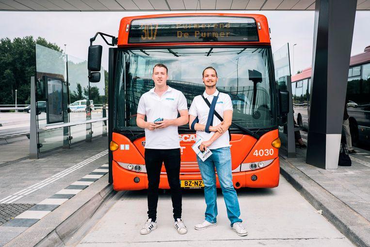 Jeffrey (22, links) en Arthur (26) helpen mensen met het nieuwe systeem. Beeld Marcel Wogram