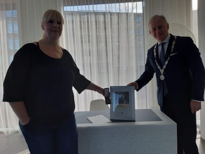 Sylvia Jannink en burgemeester Arjen Gerritsen, met een foto van Herman Jannink.