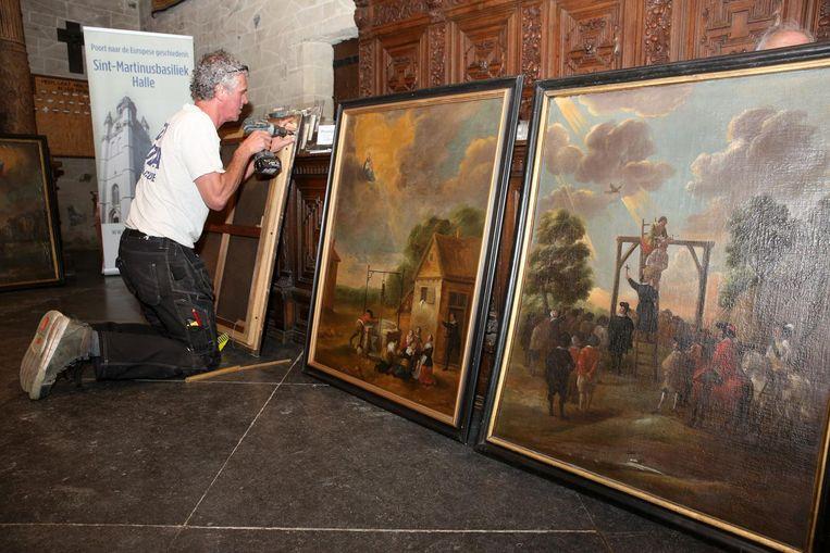 Twee mensen van een gespecialiseerde firma uit Nederland waren een hele dag in de weer om de schilderijen terug op de torenmuur te hangen.