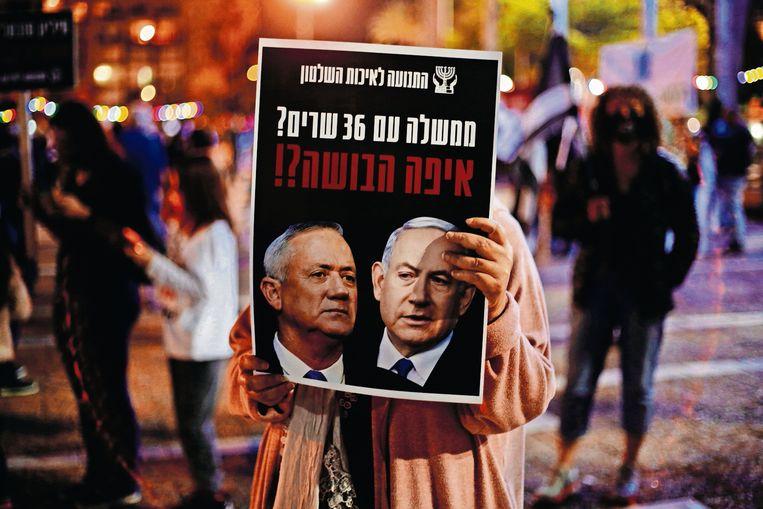 Tijdens een demonstratie in Tel Aviv tegen corruptie en de regering houdt een vrouw een bord omhoog met Gantz (links) en Netanyahu.  Beeld AP