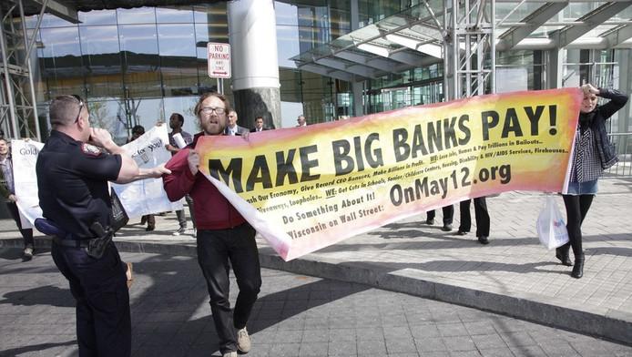 Demonstranten voor een gebouw van Goldman Sachs