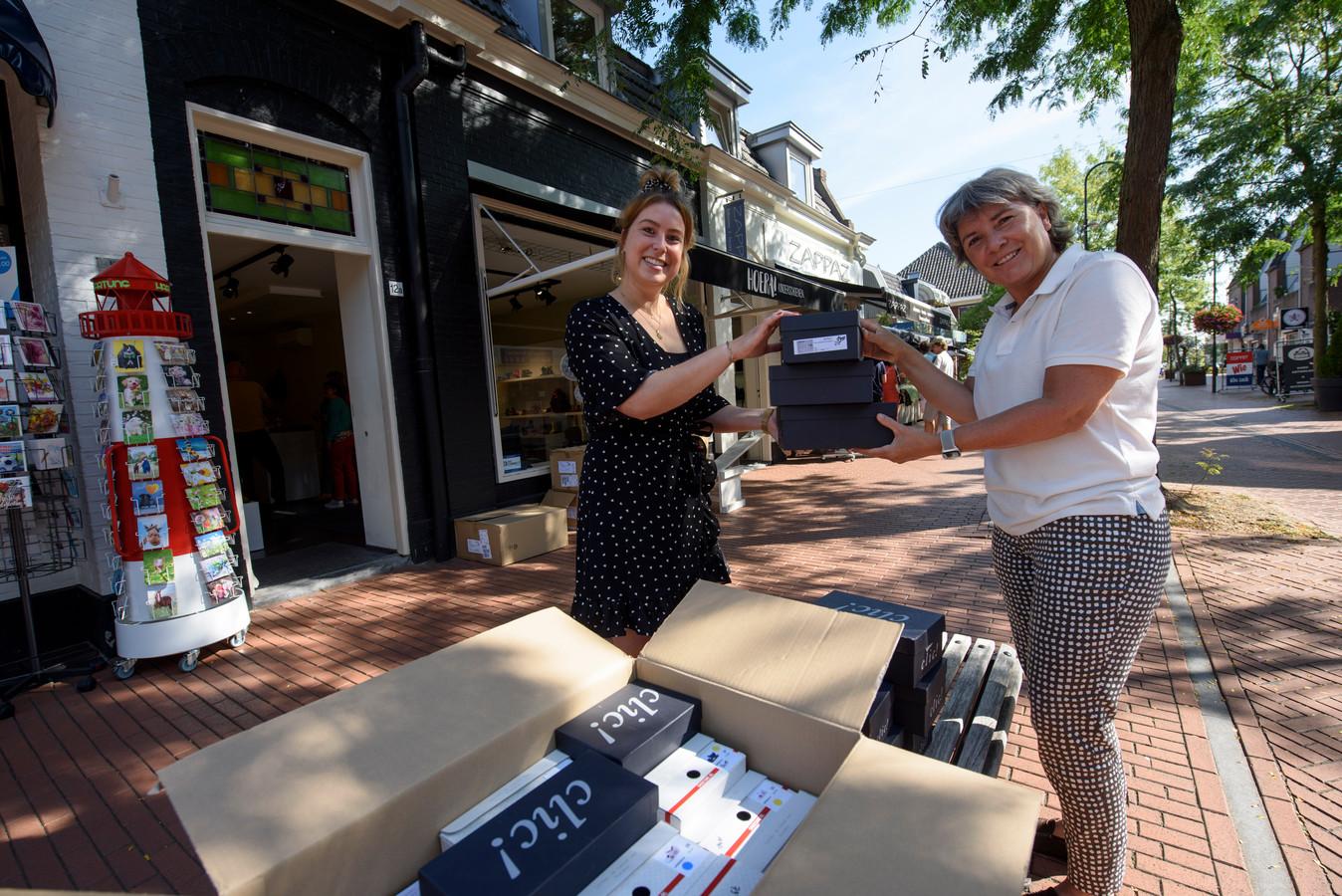 Meike Daniëls van Hoera! Kinderschoenen geeft de dozen aan Emily Zwartkruis van de kledingbank.