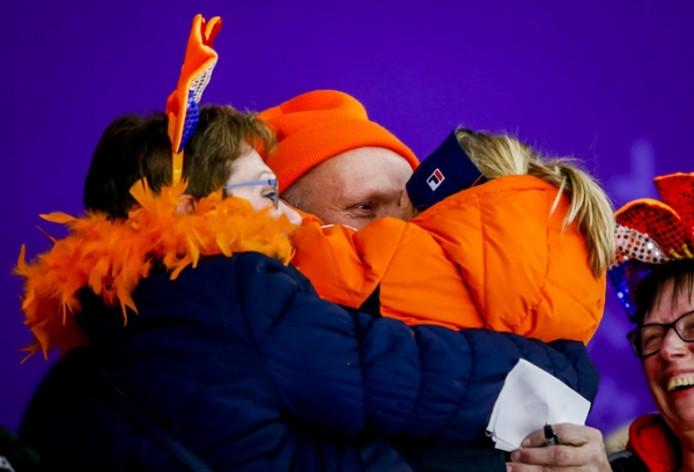 Carlijn Achtereekte valt haar vader in de armen als het goud binnen is. De vriendin van haar vader (links) deelt in de feestvreugde.