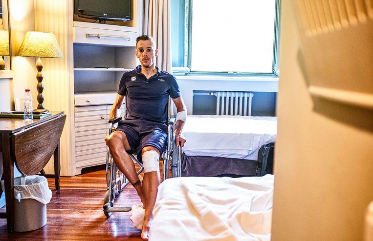 Philippe Gilbert in een rolstoel na zijn zware crash in de Tour de France. De Waal dook een afgrond in tijdens een afdaling, liep stevige averij op aan zijn linkerknie en stond wekenlang aan de kant.