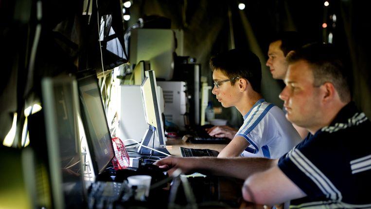 Gamers achter hun computer in een tent op CampZone, een game-evenement in de openlucht. Beeld anp