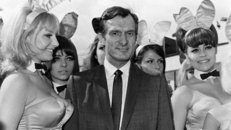 Playboy-tycoon Hugh Hefner wordt in 1966 op een vliegveld in Londen ontvangen door een groep bunny's. Beeld Getty Images