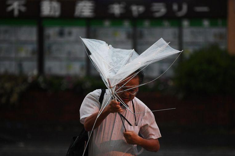 Een man vecht met zijn paraplu in Tokio.
