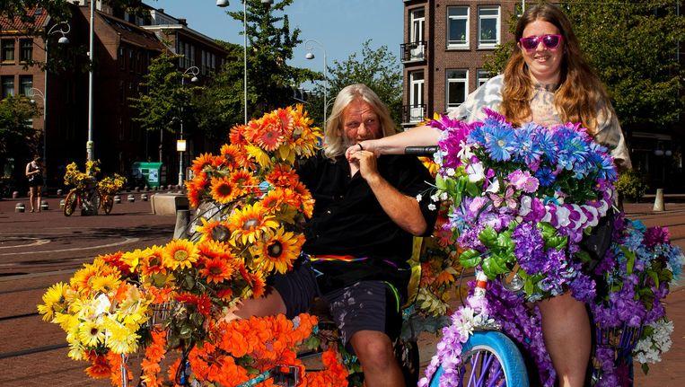 Flower bike man Warren Gregory en Michelle. 'Het liefst plaats ik de fietsen waar negativiteit moet worden gecompenseerd' Beeld Renate Beense