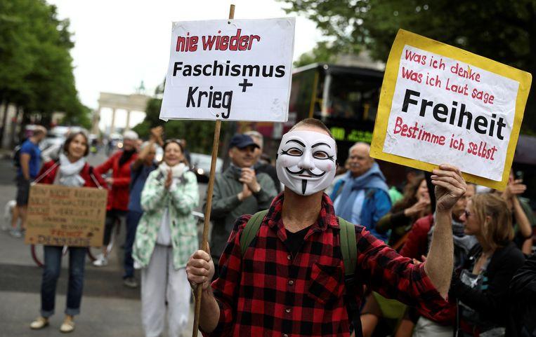 """Een demonstrant in Berlijn draagt een masker en een bord met de teksten """"Nooit meer fascisme en oorlog"""" (links) en """"Wat ik denk, wat ik luidop zeg, vrijheid bepaal ik zelf"""" (rechts)."""