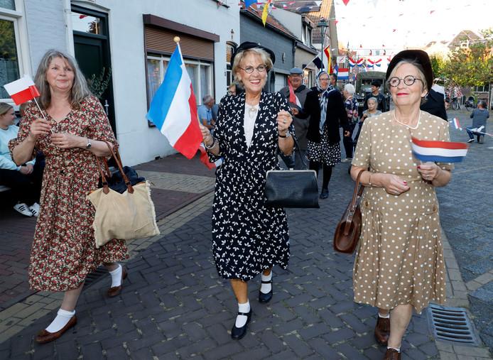 Dames in kleding jaren 40 tijdens de Vrijheidstocht in de versierde Bastionstraat