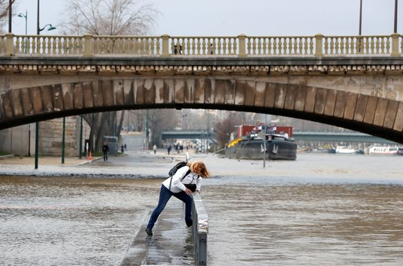 Haren in de wind, voeten in het nat. Deze vrouw trotseert het slechte weer in Parijs, waar de Seine stilaan buiten haar oevers treedt.