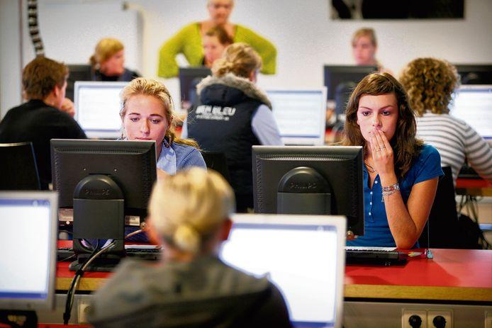 Pabostudenten maken de rekentoets achter de computer.