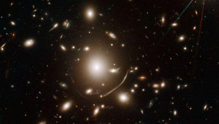 Het sterrenstelsel Abell 383 waarvan de massa het mogelijk maakt het oude en relatief zwakke sterrenstelsel dat erachter ligt waar te nemen. Foto: NASA Beeld
