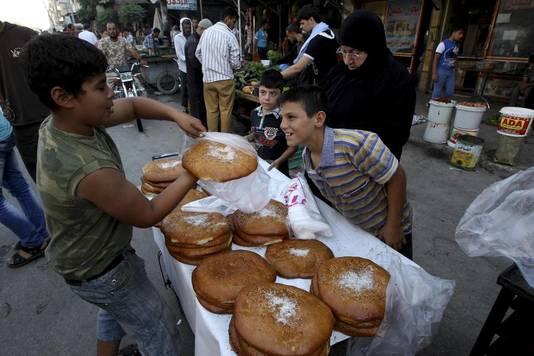 Een jongen verkoopt in Aleppo traditioneel brood om na zonsondergang het vasten mee te breken