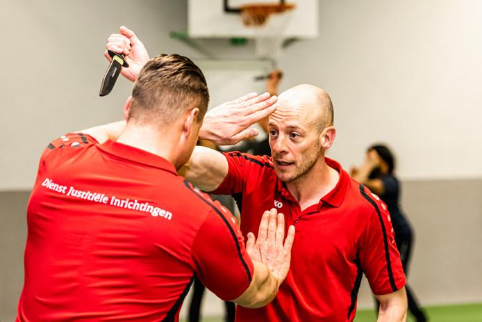 Bart (rechts) weert tijdens de clinic krav maga een aanval van collega Pieter (met nepmes) af. Bart laat zich sponsoren voor Alpe d'HuZes (fietsen voor kankerbestrijdjng) en dit was zijn tegenprestatie voor medewerkers van de Alphense gevangenis.