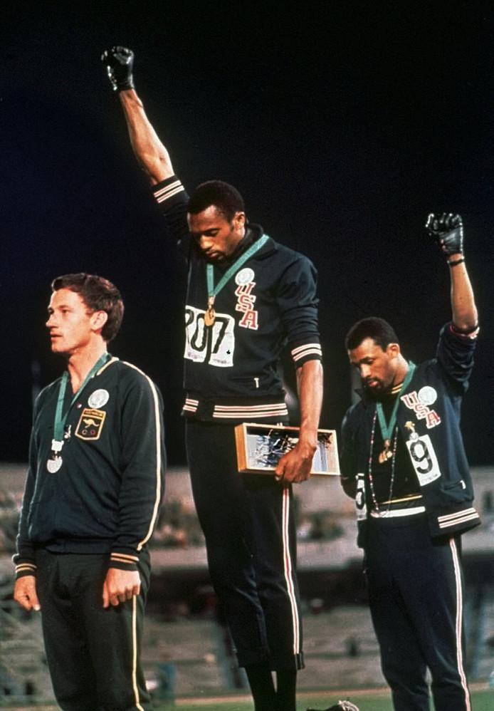 Tommie Smith, midden, en John Carlos steken een vuist omhoog en kijken naar de grond als het Amerikaanse volkslied klinkt. De Australiër Peter Norman protesteerde op zijn eigen manier.
