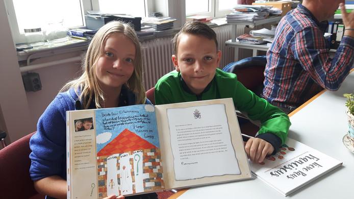 Lidewij (links) en Hannes staan met hun tekening en vraag voor de paus in het boek ''Lieve Paus Franciscus'.