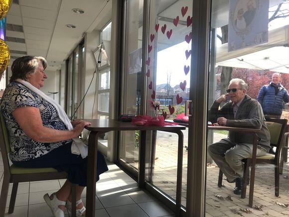Simonne en Francis vieren hun huwelijksverjaardag, elk aan een kant van het venster.