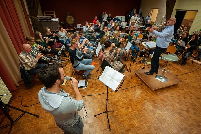 Repetitie van fanfare De Volharding in het dorpshuis voor het jubileumconcert, met gastzanger Willem Schenkelaars uit Tiel.