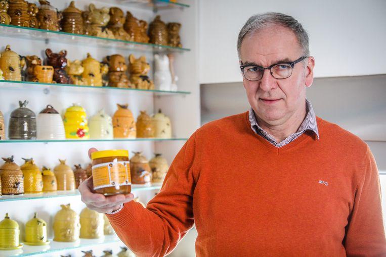 Daniël Van Rycker toont een van zijn potjes honing.