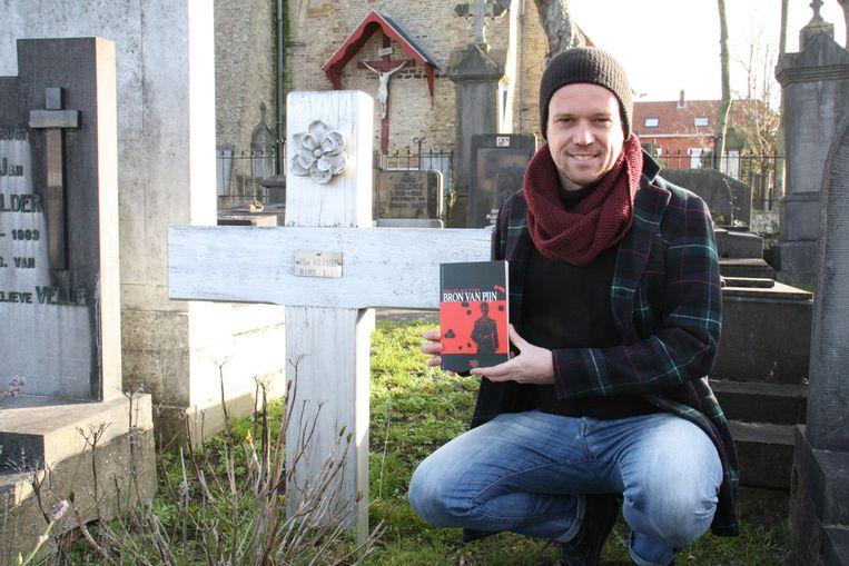 Miguel Bouttry met zijn boek 'Bron van pijn' bij het graf van zijn oma in Adinkerke.