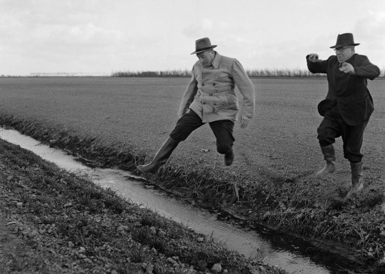 Sicco Mansholt (links) springt over een slootje bij zijn boerderij in de Wieringermeer in 1956. Beeld Nico Naeff / Nederlands Fotomuseum