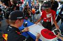 Max Verstappen zet zijn handtekening op de Japanse vlag.