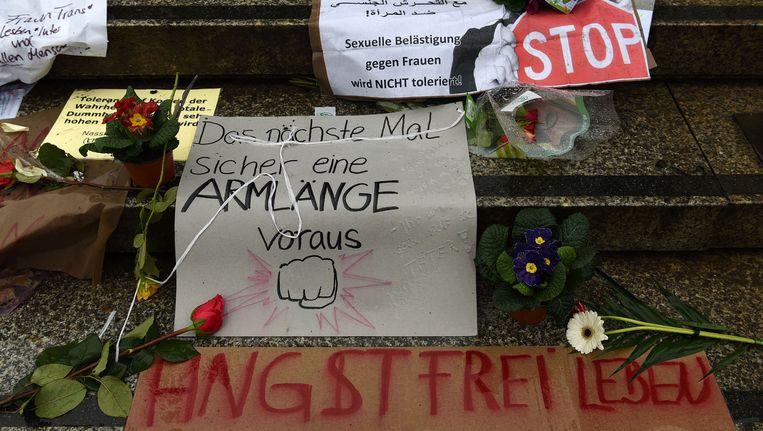 Bloemen en protestborden tegen geweld tegen vrouwen zijn neergelegd op de trappen van het station in Keulen. Beeld AFP