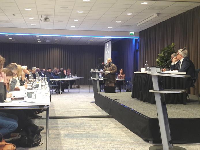 Een van de slachtoffers in de chroom-6 affaire, dhr Boutrouf, spreekt raadsleden (links) toe. Rechts luistert burgemeester Weterings mee.