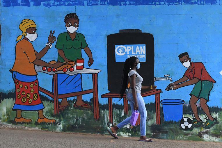 Een vrouw loopt langs een muurschildering waarop handen wassen en het dragen van mondkapjes  wordt aangemoedigd. Beeld AFP