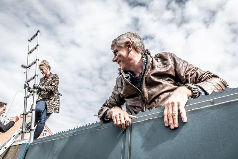 Met ladders klimmen de Vlaams Belangers over de muren en poorten van het asielcentrum.
