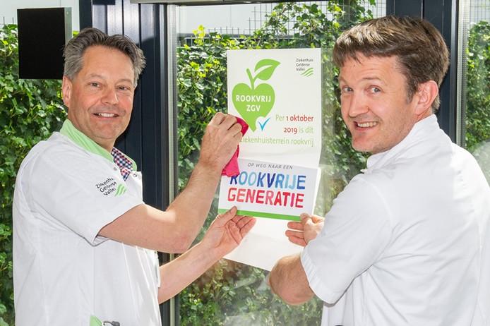 Cardioloog Maurits van der Veen en longarts Jeroen Verheul van het Edese ziekenhuis plakken de aankondiging van rookvrij ziekenhuisterrein op de rookplek.
