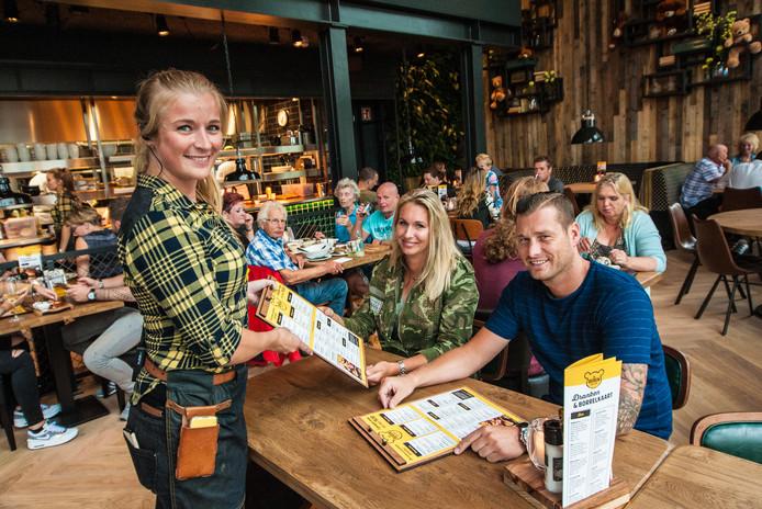 De Goudse vestiging van De Beren is nog maar net open als Cindy Groenestein (bediening) de menukaart geeft aan klanten van het eerste uur, Melissa Heyting en Melvin van der Wielen.