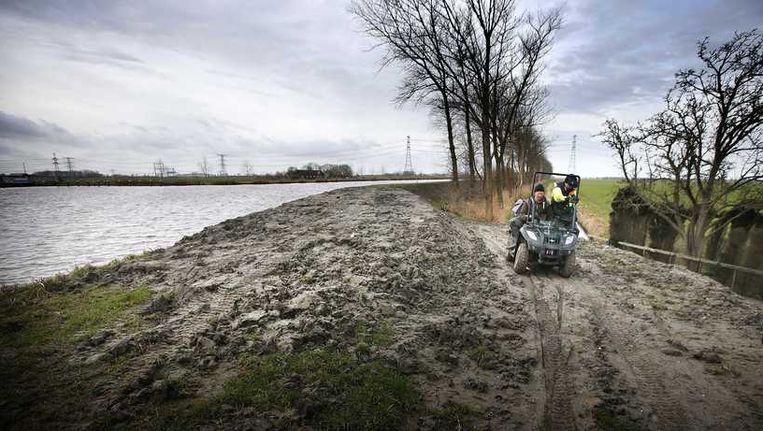 Medewerkers van het waterschap controleren de dijken langs het Eemskanaal, de dag na de nachtelijke aardbeving in noordoost Groningen. Beeld anp
