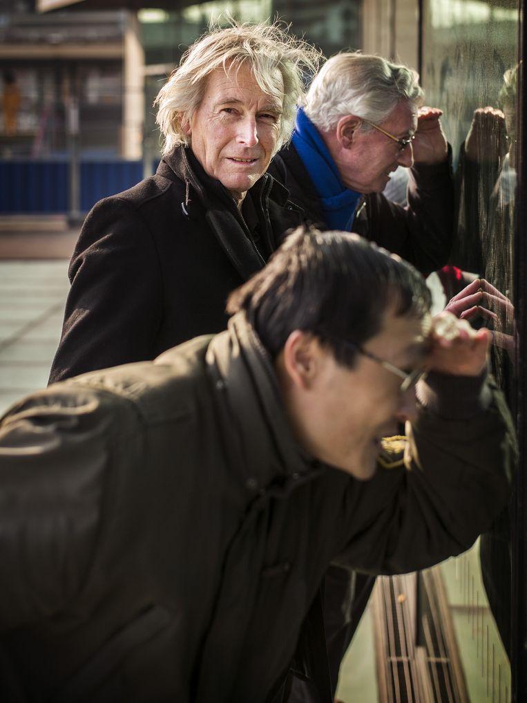 Henk de Kat, oud-verslaggever van de Delftsche Courant, tussen andere nieuwsgierigen bij de nieuwe spoorzone in Delft. Beeld Jiri Buller