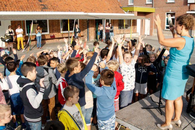 De juf steekt handen in de lucht, de kinderen volgen.